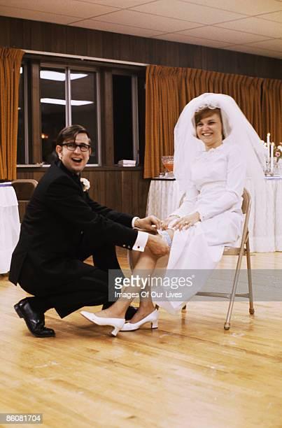 Groom taking garter off bride