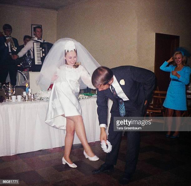 Groom taking garter off leg of bride