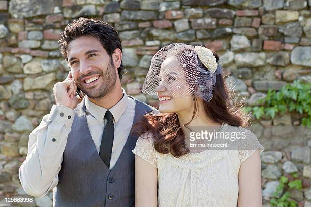 Groom talking on mobile phone next to bride