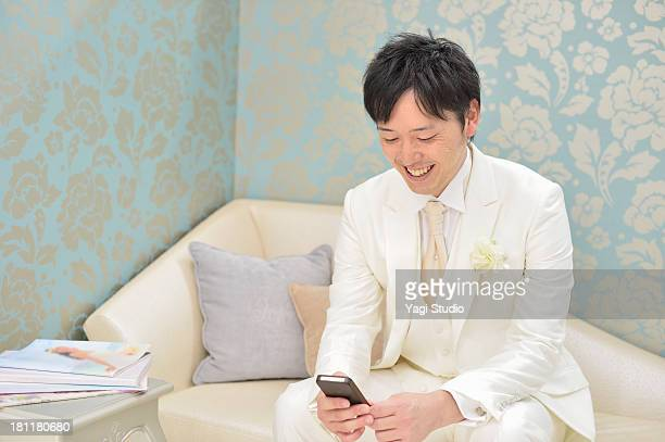 groom useing the smartphone - smoking stock-fotos und bilder