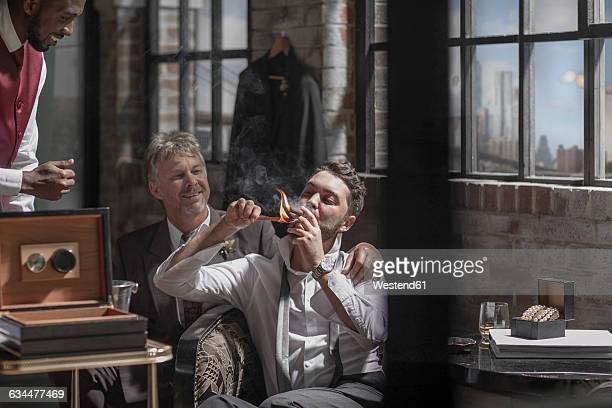 Groom with best man smoking a cigar before the wedding