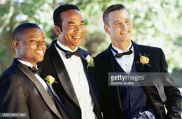 Groom with groomsmen standing in garden, posing