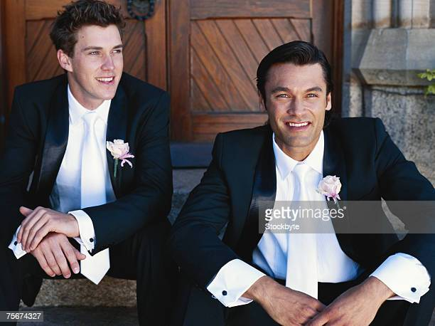 Groom with his best man sitting on steps, smiling