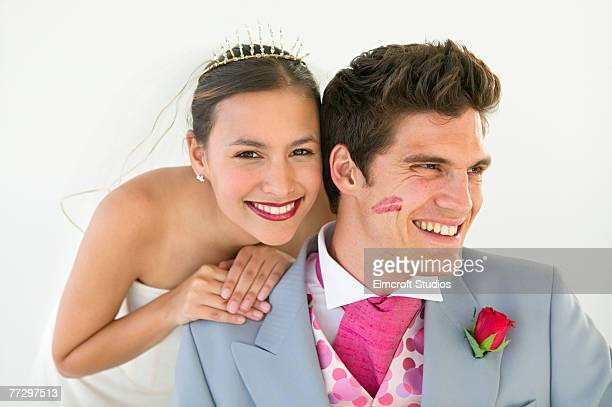 Groom with lipstick mark on cheek and smiling bride