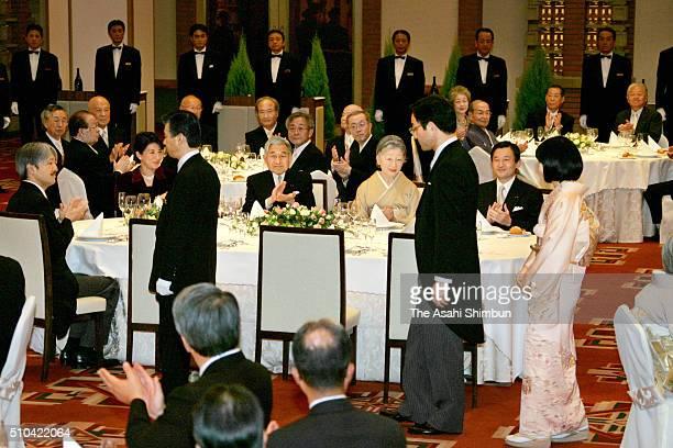 Groom Yoshiki Kuroda and bride Princess Sayako enter the room while Emperor Akihito Empress Michiko Crown Prince Naruhito Crown Princess Masako and...