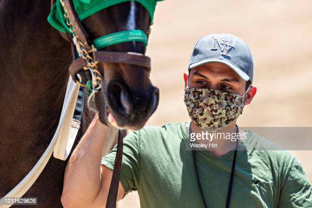 Groomer brings out a horse while wearing a mask for protection during the Covid19 Pandemic on Derby Day at Oaklawn Racing Casino Resort on May 2 2020...