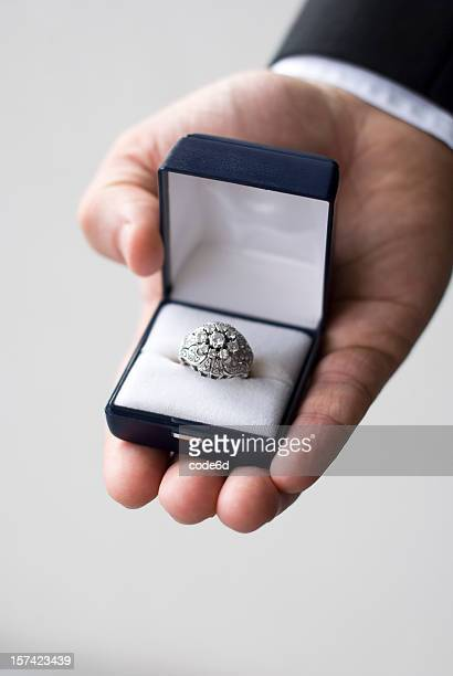 Groom's hand offering diamond engagement ring, close-up, wedding