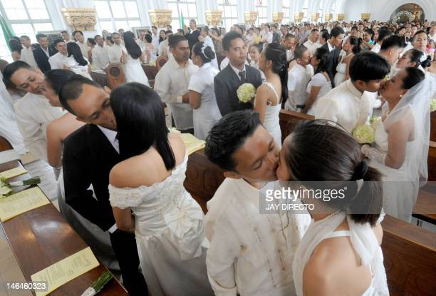 Grooms kiss their brides during a mass wedding at a University chapel in Manila on June 17 2012 Church weddings are an important part of tradition in...