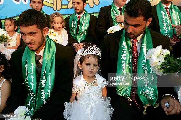 Grooms sit with young relatives on stage during a mass wedding organized by the Palestinian party Hamas August 5 2005 in Gaza City the Gaza Strip The...