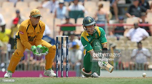 South African cricketer Herschelle Gibbs plays shot as Australia's wicketkeeper Adam Gilchrist looks on during a semifinal of ICC Cricket World Cup...