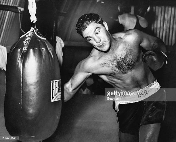 Grossinger, NY: Solid defender. World heavyweight champion Rocky Marciano gets in some licks with the big bag while training here for his forthcoming...