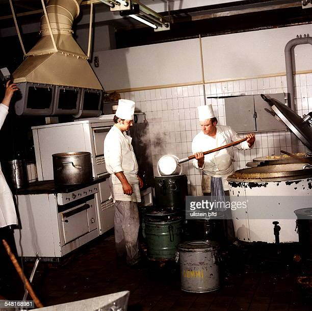 Grossküche in der Gaststätte Alextreff in Berlin zwei Köche beim Umfüllen von Speisen von einem Bottich in Kanister 1985