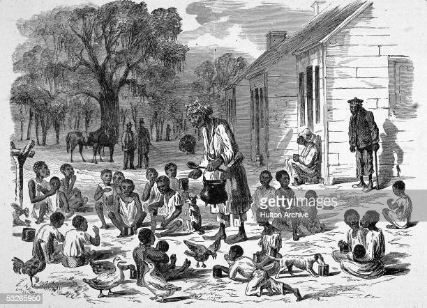 Grossly caricaturistic illustration shows an enslaved woman as she serves food to enslaved children behind the shacks in which they must live on a...