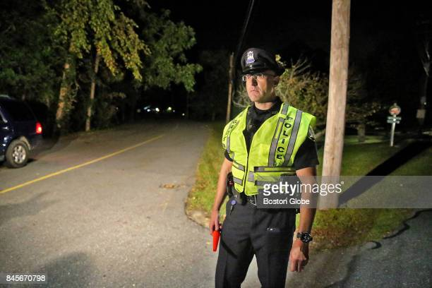 Groton police officer Mike Ratte stands on the corner of Hoilis and Common Streets blocking media access to a quadruple homicide on Common Street in...