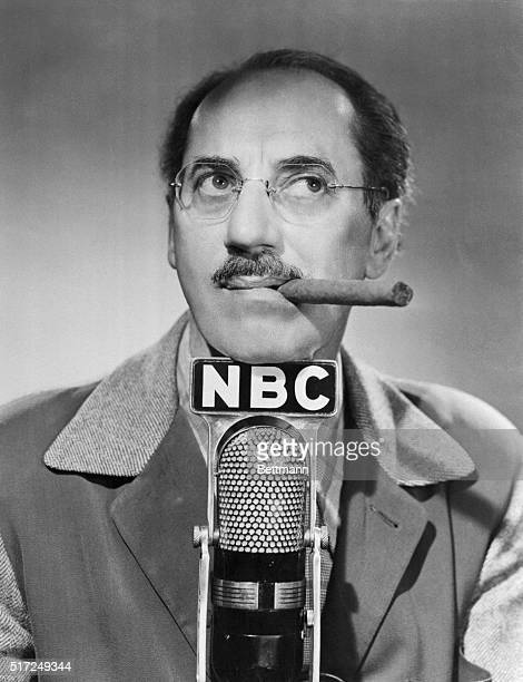 Groucho Marx adlib expert rests his chin on a microphone labeled with the call letters of his new radio home The fabulous Groucho starts his famous...