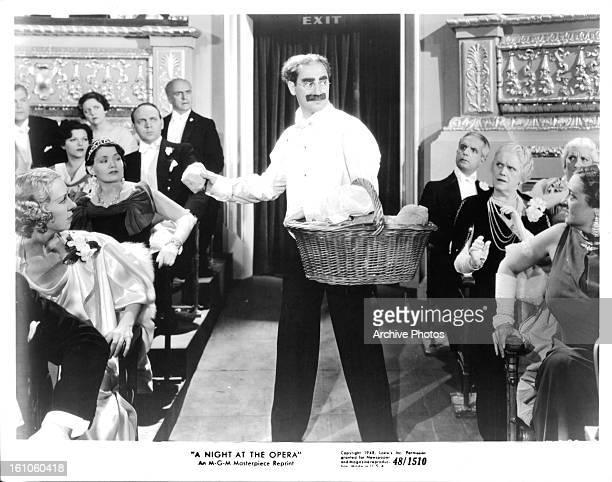Groucho Marx tossing pieces of bread in a scene from the film 'A Night At The Opera' 1935