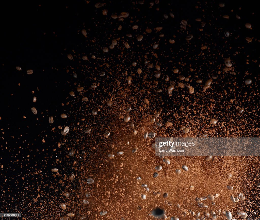 Ground coffee beans in mid-air against black background : Stock Photo