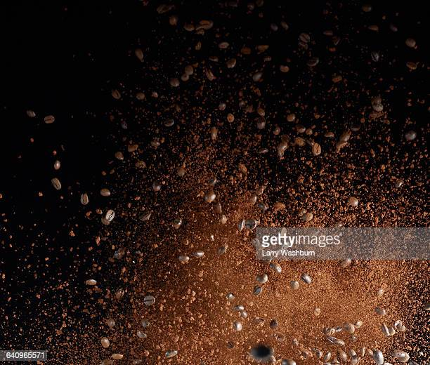 ground coffee beans in mid-air against black background - ground coffee stock photos and pictures