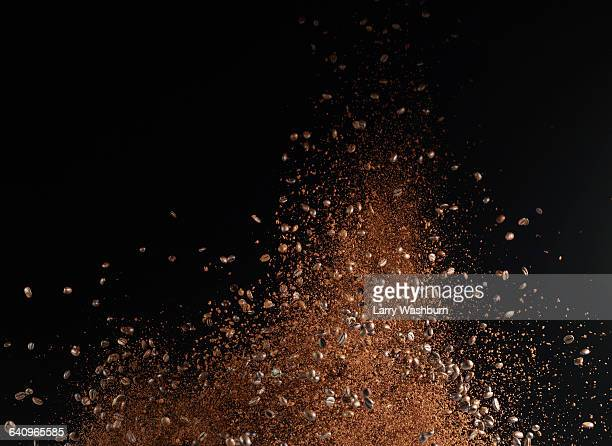 ground coffee beans in mid-air against black background - café moulu photos et images de collection