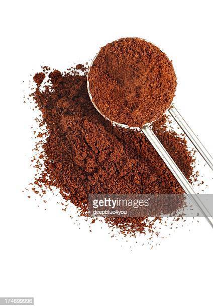 ground coffee pile with spoon isolated - ground coffee stock photos and pictures