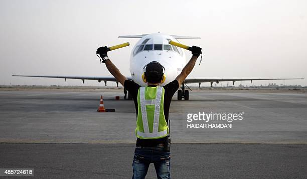 A ground controller directs an airliner on the apron on August 29 2015 at the international airport of the city of Najaf as Iraqis are heading to...