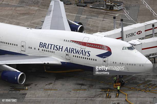 Ground crew attend to a passenger aircraft operated by British Airways a unit of International Consolidated Airlines Group SA as it sits parked at...