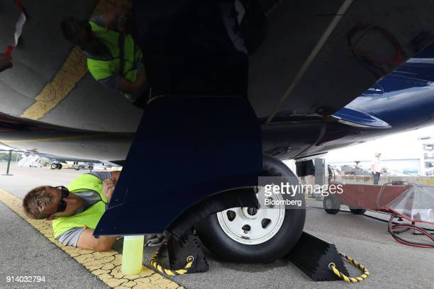 A ground crew cleans the tire of an Embraer SA Phenom 300 aircraft on display during a media preview day at the Singapore Airshow held at the Changi...