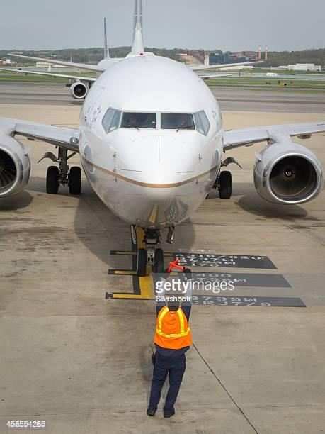 Ground crew directing jet onto ramp.