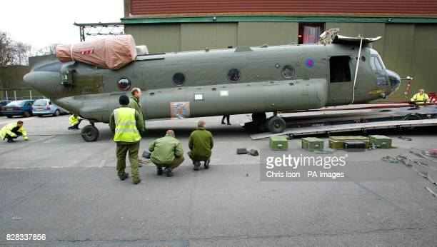 Ground crew ease an RAF Chinook helicopter from 18 Squadron onto a low loader while the helicopter crew watch at RAF Odiham in Hampshire, Tuesday...
