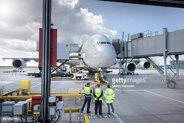 ground crew inspecting a380 aircraft on stand in airport - monty rakusen stock photos and pictures