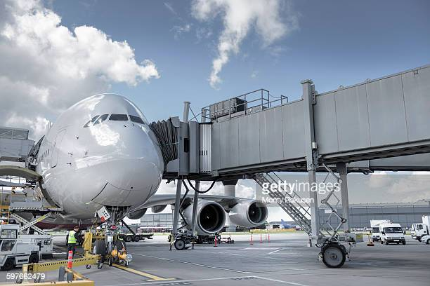Ground crew inspecting A380 aircraft on stand in airport