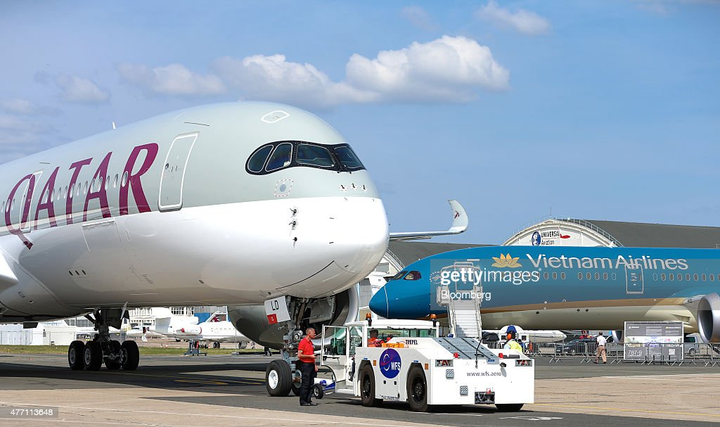 Ground crew manoeuvre an Airbus SAS A350 aircraft, operated by Qatar Airways Ltd., left, into position near a Boeing Inc. 787-9 Dreamliner, operated by Vietnam Airlines Corp., during preparations ahead of opening at the 51st International Paris Air Show in Paris, France, on Sunday, June 14, 2015. The 51st International Paris Air Show is the world's largest aviation and space industry exhibition and takes place at Le Bourget airport June 15 - 21. Photographer: Jasper Juinen/Bloomberg via Getty Images
