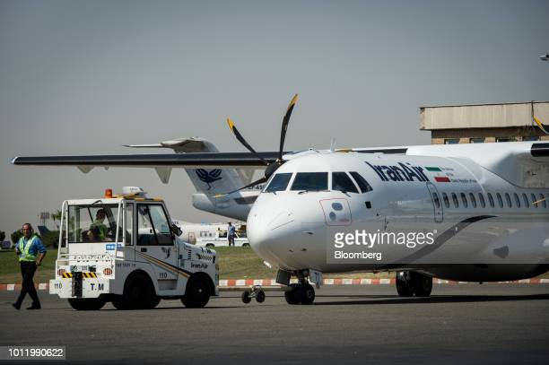Ground crew manouver a new twin engine ATR 72600 turboprop aircraft after landing at Mehrabad International airport in Tehran Iran on Sunday Aug 5...
