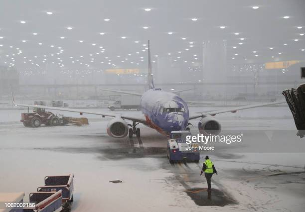 A ground crew member approaches a cancelled flight due to a snow storm at the Newark Liberty International Airport on November 15 2018 in Newark New...