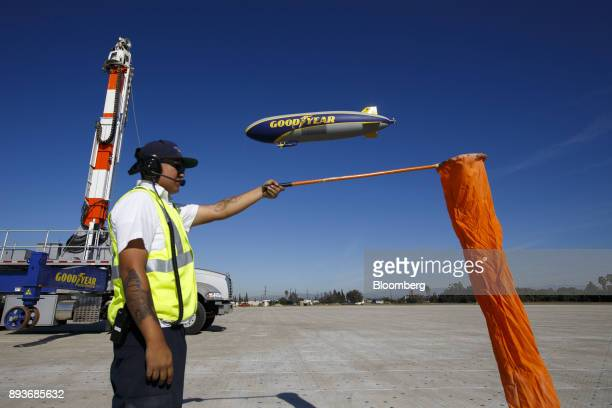 A ground crew member checks the wind as the Goodyear Tire Rubber Co Wingfoot Two blimp arrives at the company's airship base in Carson California US...