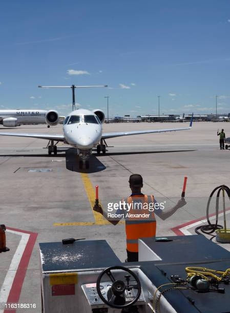 A ground crew member directs a United Express plane into its gate at Denver International Airport in Denver Colorado