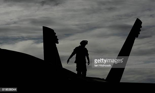 Ground crew member from the United States Navy VFA115 squadron inspects the tail of a FA/18E Super Hornet in its hangar at the Townsville airport on...