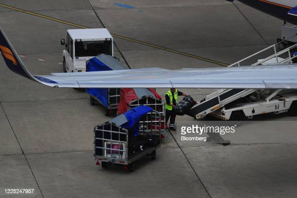 Ground crew member loads luggage into the cargo hold of a passenger aircraft, operated by Air Iceland, at Tegel Airport, operated by Flughafen Berlin...