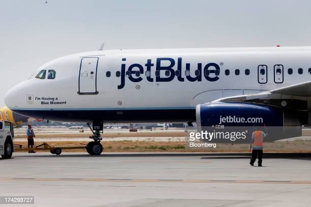 A ground crew member prepares a JetBlue Airways Corp plane for takeoff at Long Beach Airport in Long Beach California US on Monday July 22 2013...