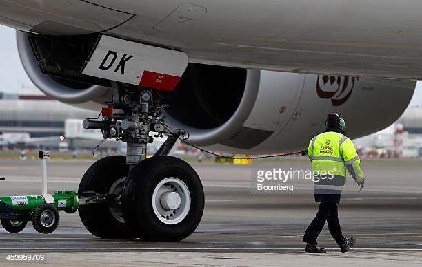 A ground crew member walks near the front landing gear of an Airbus A380800 aircraft operated by Emirates as it taxis away from Terminal 3 of...