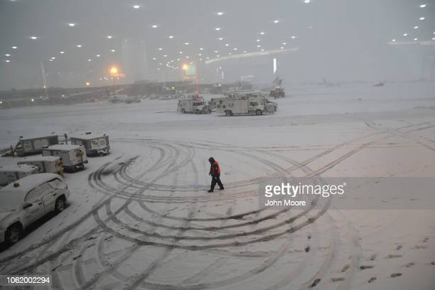 A ground crew member walks through the snow at the Newark Liberty International Airport on November 15 2018 in Newark New Jersey The early season...