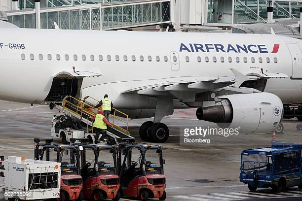 Ground crew members connect a baggage conveyor to an Air France aircraft operated by Air FranceKLM Group at Charles de Gaulle airport operated by...