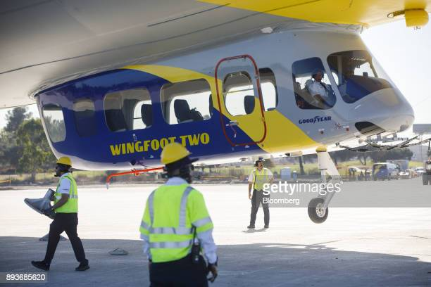 Ground crew members guide the Goodyear Tire Rubber Co Wingfoot Two blimp as it arrives at the company's airship base in Carson California US on...