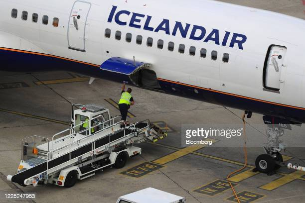 Ground crew prepare to load luggage into the cargo hold of a passenger aircraft, operated by Air Iceland, at Tegel Airport, operated by Flughafen...