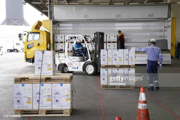 Ground crew prepare to transport refrigerated shipping containers carrying the Pfizer-BioNTech Covid-19 vaccine to a truck after its arrival at...