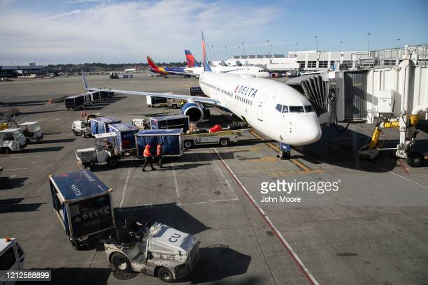Ground crew prepares to unload luggage from an arriving Delta Airlines flight at the Seattle-Tacoma International Airport on March 15, 2020 in...