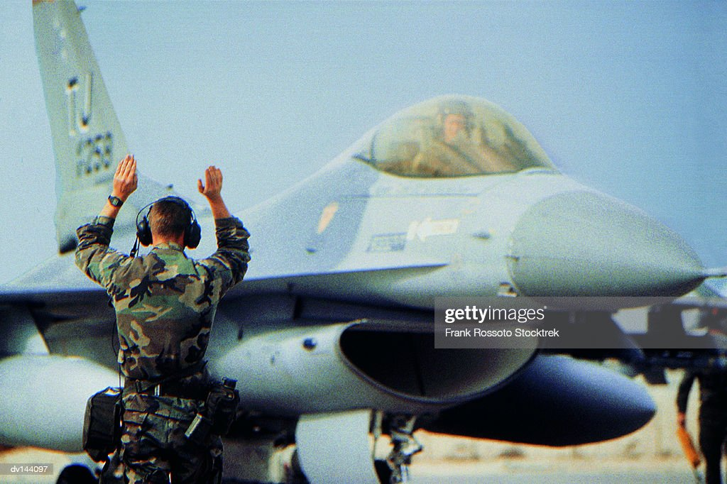 Ground crew signalling to pilot of a Military Airplane : Stock Photo
