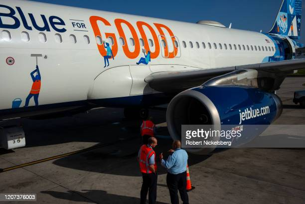 Ground crew staff observe an arriving JetBlue Airways plane from New York City at the Maurice Bishop International Airport in St. Georges, Grenada...