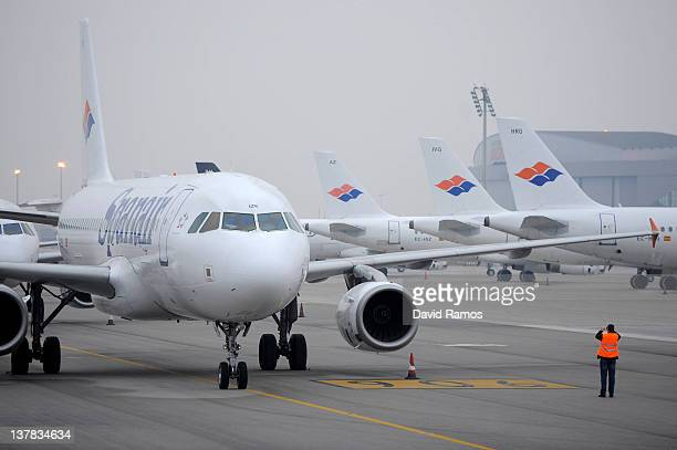 A ground crew staff takes pictures of Spanair airplanes stand parked on the tarmac at the El Prat International Airport in Barcelona on January 28...
