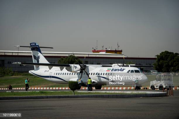 Ground crew stand beside a new twin engine ATR 72600 turboprop aircraft right after landing at Mehrabad International airport in Tehran Iran on...